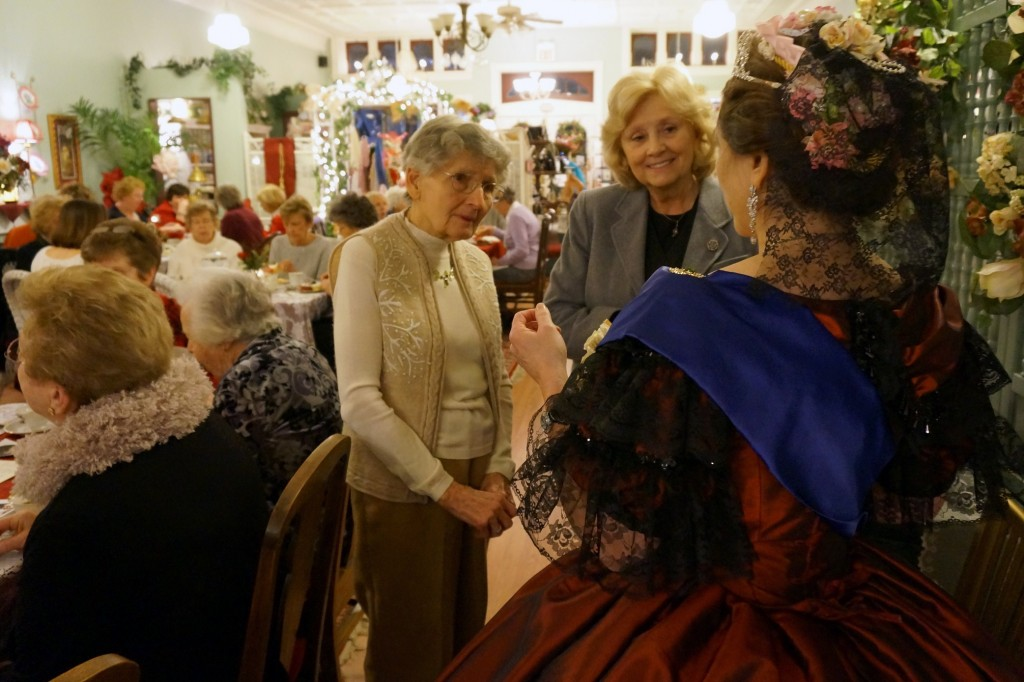 HSR members Nancy Hall, left, and Linda McCormick, middle, compliment our guest. Look at the rich detail  of the hair ornamentation.
